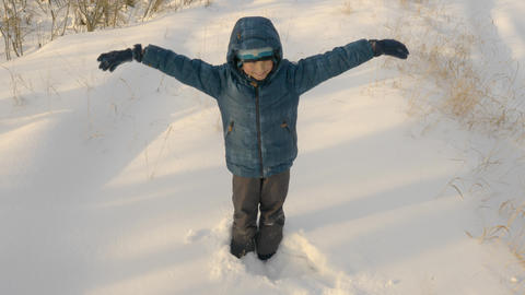 Little kid making snow angel lying down on snow Live Action