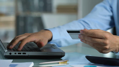 Man making online payment on computer, using card for internet banking services Live Action