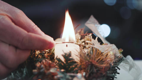 Close-up of a man's hand lighting a candle Archivo