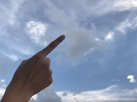 woman use her right forefinger pointing up in the bright blue sky with white Photo