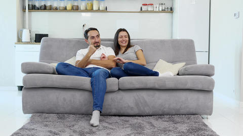 The husband and wife sit on the couch Footage