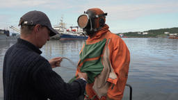 Sailor helps to put on dry diving suit to scuba diver before diving into ocean Footage