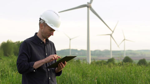Worker stands near white wind turbines, typing on a tablet. Windmills, green Footage