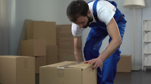 Moving company worker carefully packing and carrying boxes, quality services Footage