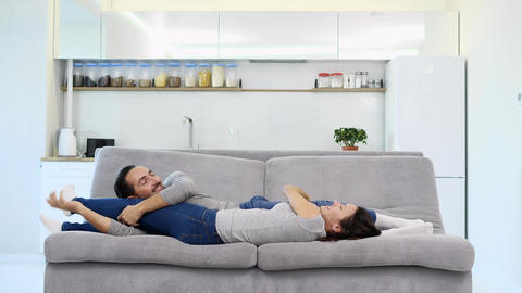A husband and wife sleep on a sofa Archivo