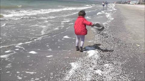 boy walking on a winter beach GIF