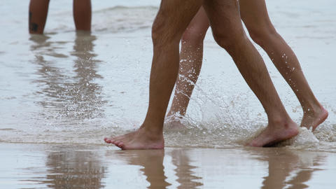 Couple beach walking, legs close-up