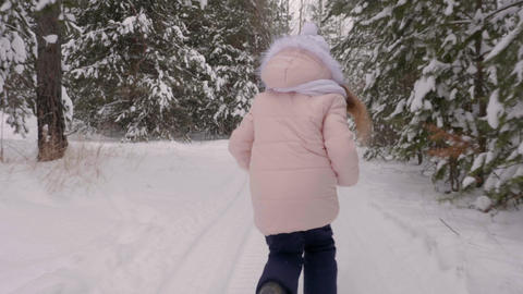 Teenage girl running through snowy forest Live Action