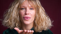 Closeup portrait of young charming caucasian female making an air kiss to the Footage