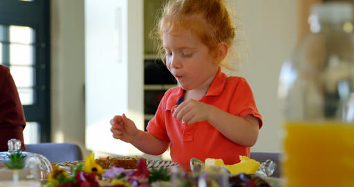 Cute little boy eating cake at dining table 4k Live Action