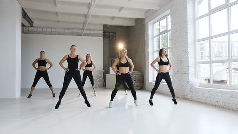 In fitness class group a of six young women in black sports suits perform Footage