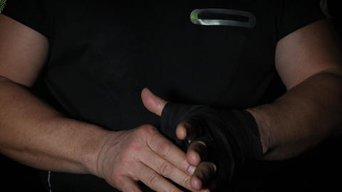 man wraps his hands in black textile bandage for sports, close up, slow motion Archivo