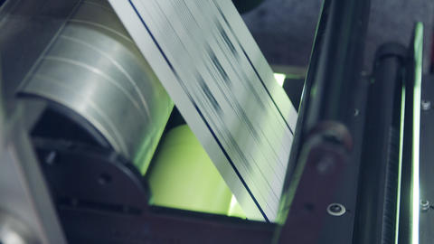 Closeup on paper moving through a large industrial printing machine Live Action