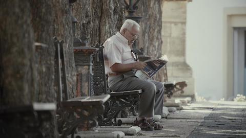 VALENCIA, SPAIN - SEPTEMBER 22, 2018. Elder man sitting on park bench and GIF