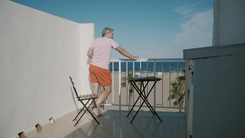 Man enjoys sea view from a hotel terrace on summer vacation GIF