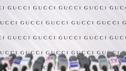 Press conference of GUCCI, press wall with logo and microphones, conceptual GIF