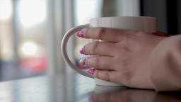 Coffee cup close up with woman's hands around it. Sitting in a tea shop holding Footage