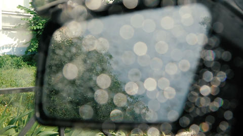 The side window of the car is lowered with rain stones on it - slow motion GIF
