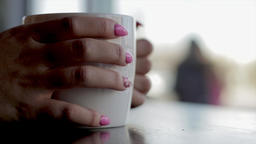 Close up of female hands with manicured nails holding a coffee mug watching 영상물