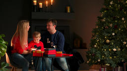 Portrait of happy family opening a Christmas present gift box in the evening Archivo