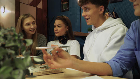 Students share their impressions and discuss sitting at a table with books in a Live Action