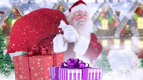 Santa clause and christmas presents in front of decorated houses in winter scenery combined with fal Live Action
