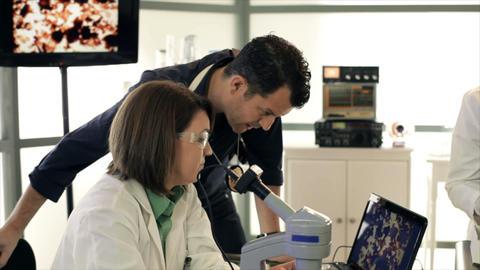 CSI team looking at evidence on microscope Footage