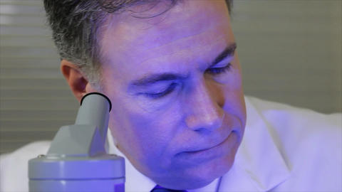 lab tech looks in microscope wide Footage