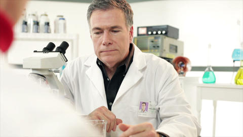 Scientist giving paperwork to a tech Footage