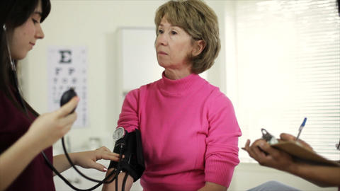 Nurses Taking Blood Pressure And Writing Notes stock footage