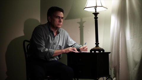 man writing at a small desk Footage
