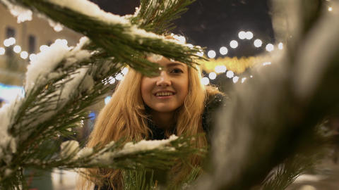 Happy cheerful girl near fir-tree branch in snow Christmas tree branches with Live Action