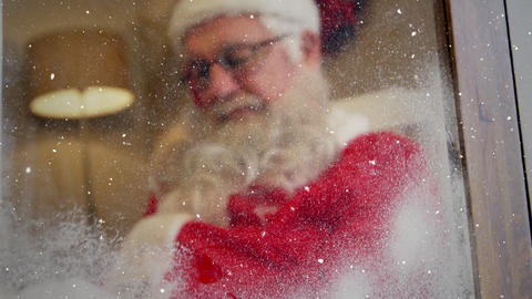 Video composition with falling snow over santa asleep in room Animation
