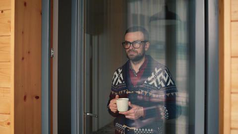 Man drinking tea or coffee near the window and looking through the glass 영상물