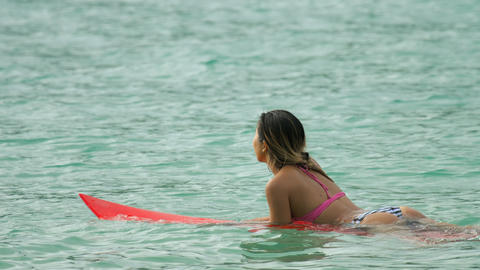 Attractive surfer woman on a surfboard floating in ocean Footage