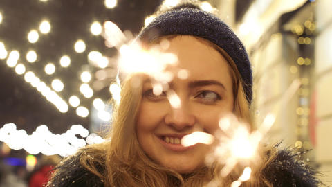 Close up portrait of cheerful pretty woman with sparklers in hands close up Footage