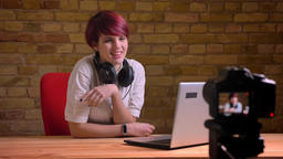 Portrait of young short-haired female blogger joyfully talking into camera on Footage