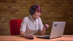 Portrait of young short-haired female streamer in headphones gets extremely Footage
