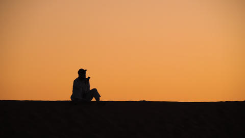 Man on sand dune talking on mobile phone Footage