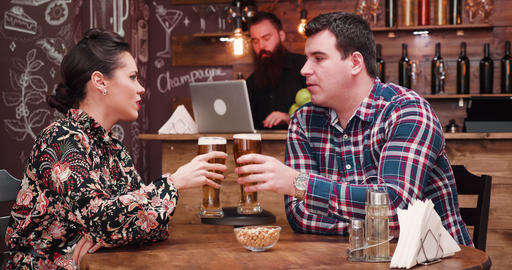 Happy smiling couple clink their glasses with beer GIF