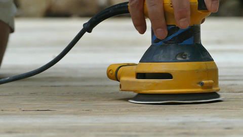 Sanding wooden deck outside with power sander in slow motion GIF