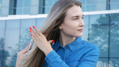 Charming lady trying to comb brush her hair in a heavy wind Footage