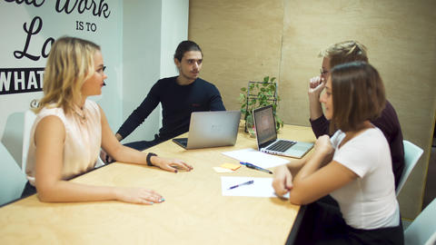 Small group of entrepreneurs meet to discuss new strategies in business using Footage