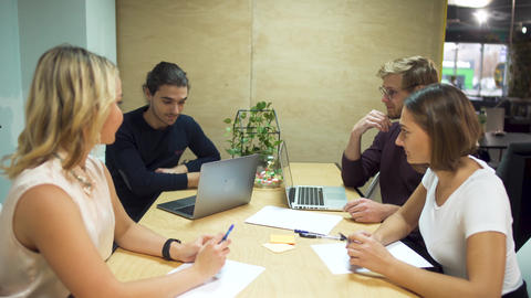 Four young entrepreneurs discuss new strategies in start-up using laptops in Footage