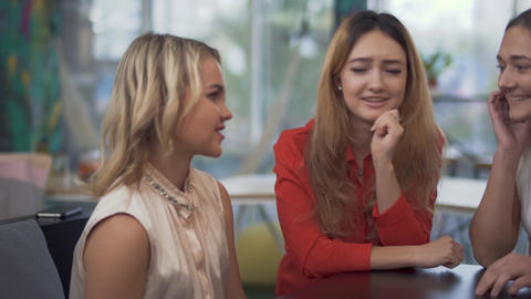 Three cheerful girls sitting at boardroom table during a break in a business Live Action