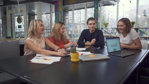 Four young adult entrepreneurs discuss new strategies in start-up using laptops Footage