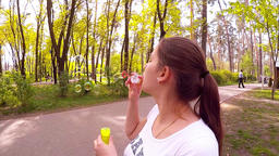 Charming pregnant girl playing with soap bubbles in the park ビデオ