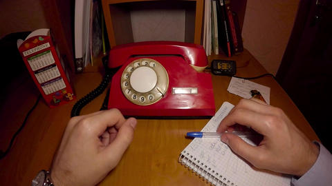 A man is ringing on an old red phone Archivo