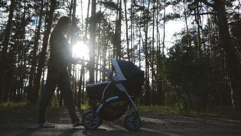 Slow motion - Slender mother walks with a stroller in the forest in the sun ビデオ