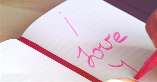 Woman Hand Writes On The Notebook Words I LOVE YOU Footage